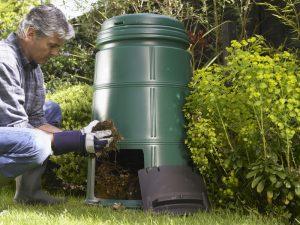 Gardener tending garden and removing soil from compost bin